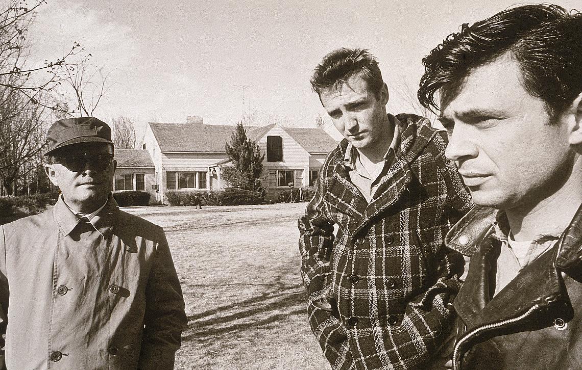 """Tруман Капоти (1924 - 1984) (вляво), облечен в гащеризон, очила и шапка, стои на тревата близо до американските актьори Скот Уилсън и Робърт Блейк (вдясно) при заснемането на филмовата адаптация на книгата """"Хладнокръвно"""""""